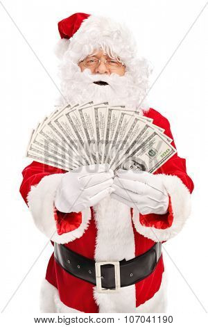 Vertical shot of Santa Claus spreading a stack of money and looking at the camera isolated on white background