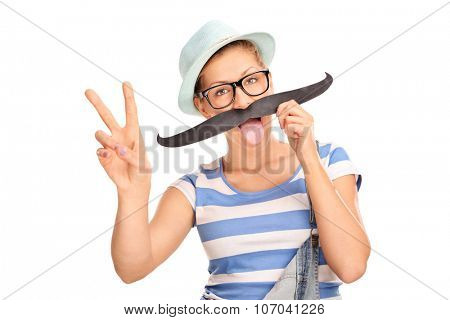 Hipster girl holding fake mustache on her face and making a peace hand sign isolated on white background