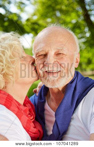 Happy woman kissing old man on the cheek in a summer garden