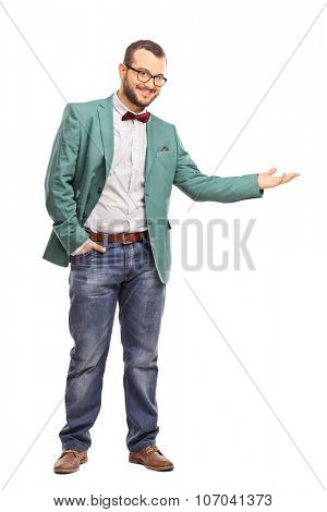 Full length portrait of a fashionable guy gesturing with his hand and looking at the camera isolated on white background
