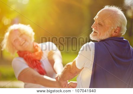 Happy senior couple dancing in the sun in summer in nature