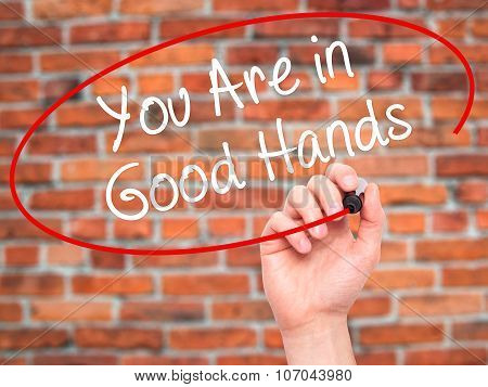 Man Hand writing You Are in Good Hands with black marker on visual screen.