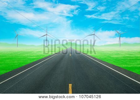 Asphalt Road Through The Green Field With Wind Turbine And Blue Sky