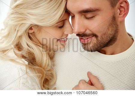 family, love, winter and people concept - close up of happy couple faces with closed eyes