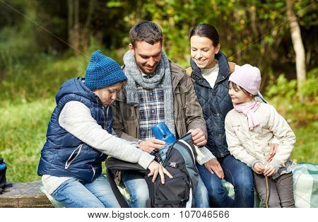 camping, travel, tourism, hike and people concept - happy family with backpack and thermos at camp