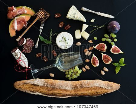 Wine and snack set. Baguette, glass of white, figs, grapes, nuts, cheese variety, meat appetizers, h