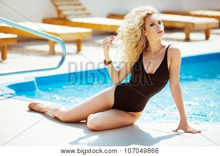 Wellness. Bikini Model. Beautiful Sexy Woman With Wavy Hair In Black Bikini Posing And Sunbathing By