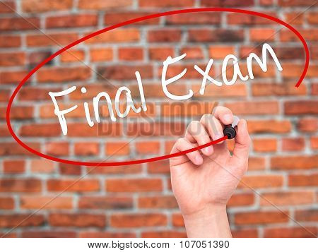 Man Hand writing Final Exam with black marker on visual screen.