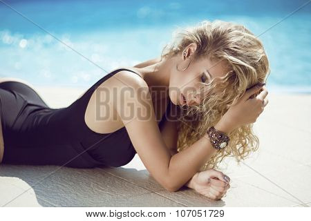 Fashion Portrait Of Beautiful Tanned Woman With Blond Hair In Elegant Black Bikini Relaxing Beside B