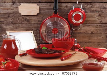 red theme lunch : fresh grilled bbq roast beef steak red plate green chili tomato soup ketchup sauce paprika small glass ground peppercorn modern cutlery served wooden plate empty nameplate menu board