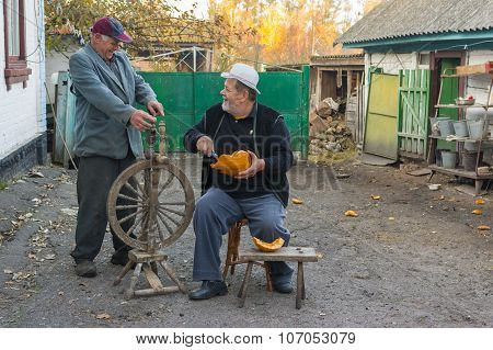 Two elderly peasant discuss politic news while working outdoors.