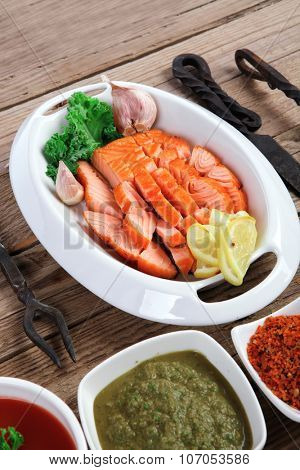 breakfast delicious portion of fresh roast salmon fillet with green chili sauce tomato soup dry spices over wooden table with black forged handmade cutlery - healthy food, diet cooking concept
