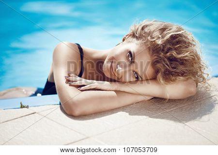 Attractive Young Smiling Girl Model Sunbathing And Tanned In Blue Swimming Pool On Summer Vacation.