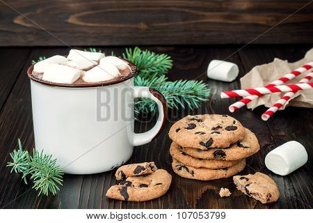 Hot chocolate with marshmallows and chocolate chip cookies over dark wooden background.