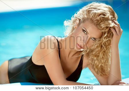 Fashion Sexy Tanned Blond Woman Sunbathing In Blue Water Swimming Pool, Model With Curly Hair Posing