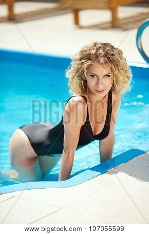 Beautiful Sensual Woman In Bikini Resting And Tanned In Blue Swimming Pool. Hot Summer Outdoor Portr