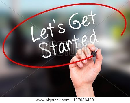 Man Hand writing Lets Get Started with black marker on visual screen.