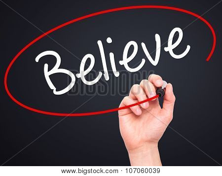 Man Hand writing Believe with black marker on visual screen.