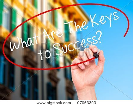 Man Hand writing What Are The Keys to Success? with black marker on visual screen.