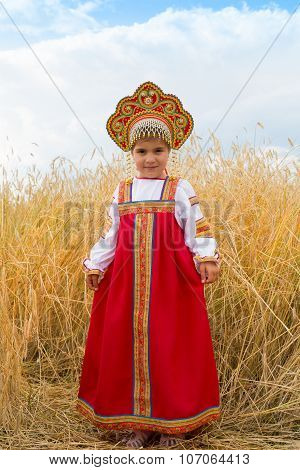 Girl In Russian National Dress With Ears In Hands Stand In The Field Of The Ripening Wheat
