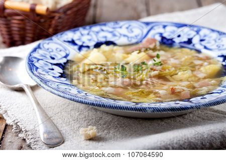 Cabbage soup with bacon, potato, meat, ceramic plate, bread