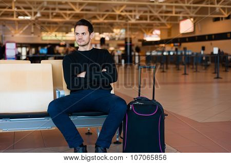 Portrait of handsome smiling man in casual wear at airport