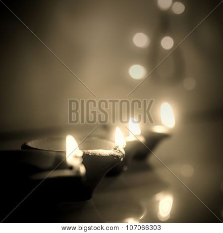 Diwali Greeting card background. Monochromatic image of glowing traditional Indian lamps.