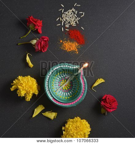 Traditional Indian lamp, marigold flowers, and kumkum tilak. Indian religious festive background. View from top.