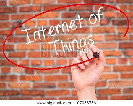 Man Hand writing Internet of Things with black marker on visual screen.