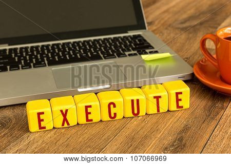 Execute written on a wooden cube in front of a laptop