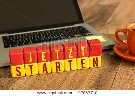 Start Now (in German) written on a wooden cube in front of a laptop