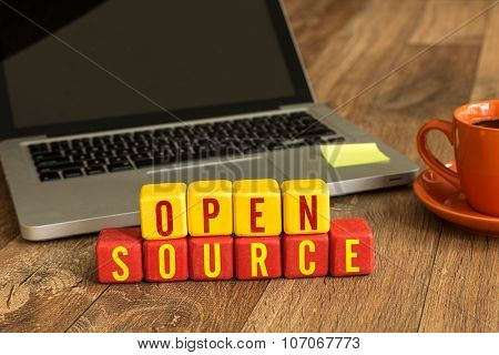 Open Source written on a wooden cube in front of a laptop