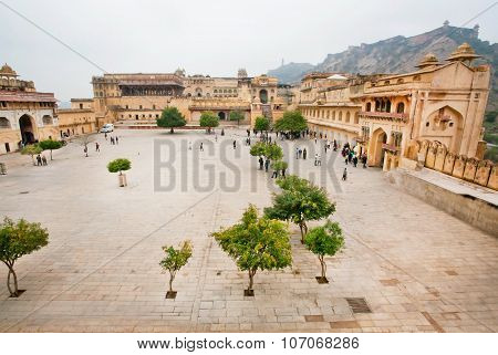 Tourists came to the courtyard with trees and historical structures of Amber Fort in India