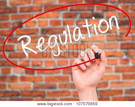 Man Hand writing Regulation with black marker on visual screen