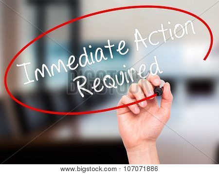 Man Hand writing Immediate Action Required with black marker on visual screen.