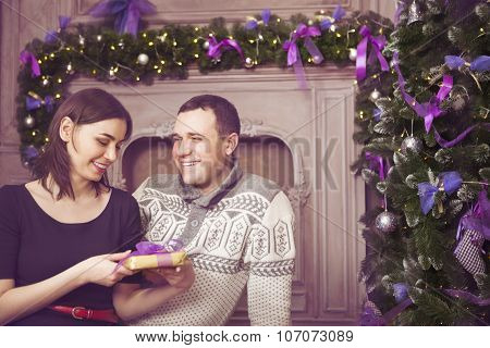 Beautiful Young Couple With Present Near Christmas Tree