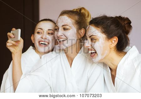 Three Young Happy Women With Face Masks At Spa Resort. Frenship And Wellbeing Concept
