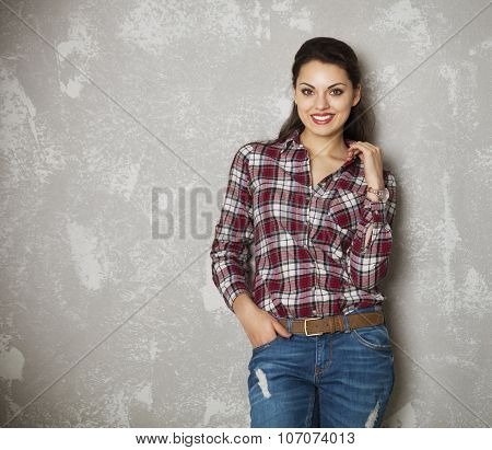 Young Woman Leaning Against A Gray Wall Looking At Camera