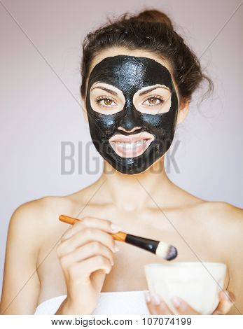 Young Woman Applying A Mask For The Face Of The Therapeutic Black Mud