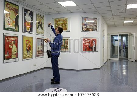 ST. PETERSBURG, RUSSIA - OCTOBER 24, 2015: Tourist making photo of beer posters at the Baltika - St Petersburg brewery during the October Beer Festival. The brewery is providing guided tours to plant