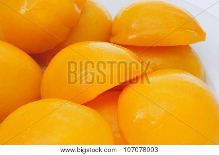 closeup of some peeled and halved peaches in syrup in a white plate