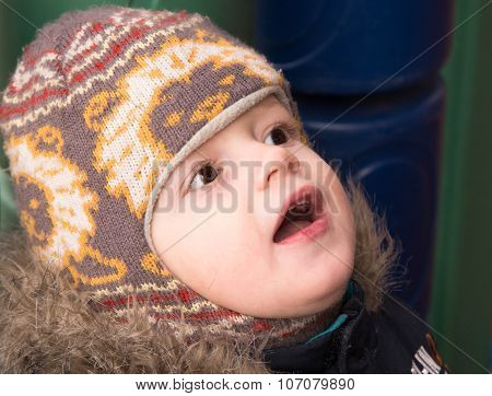 The Little Boy In A Warm Cap With Astonishment Looks Up