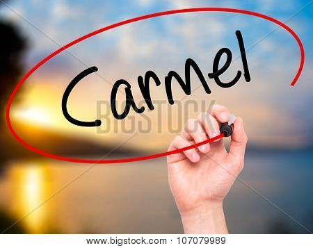 Man Hand writing Carmel with black marker on visual screen.