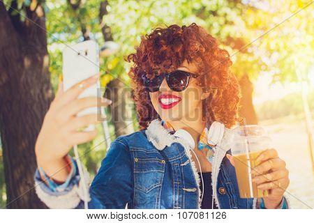 Curly readhead teenage girl with takeaway coffee taking a selfie
