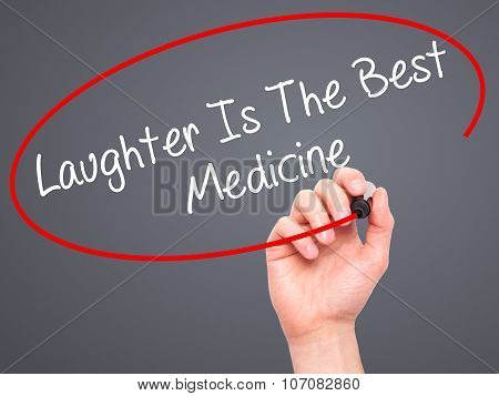Man Hand writing Laughter Is The Best Medicine with black marker on visual screen.