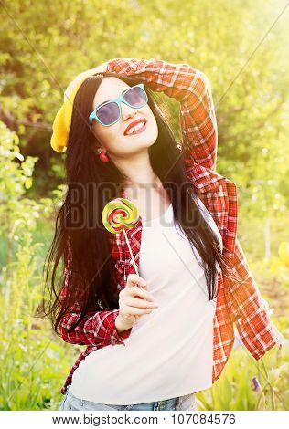 Fashion Girl Hipster In Glasses And Shirt With Candy Outdoors