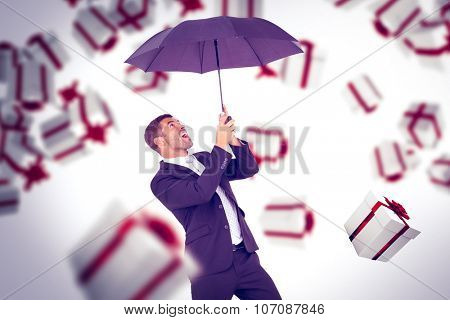 Businessman sheltering under black umbrella against white and red gift box