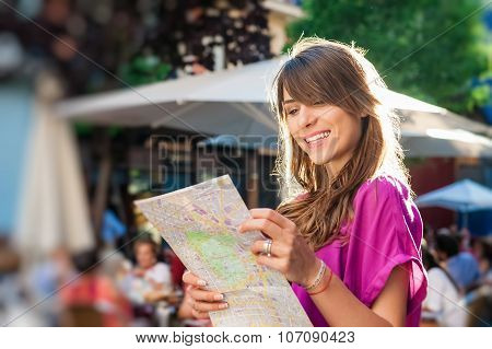 Young woman tourist holding a paper map