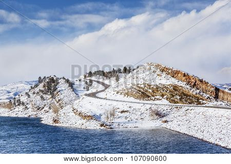 mountain lake, rock cliff, dam and windy road in winter scenery - Horsetooth Reservoir near Fort Collins, Colorado