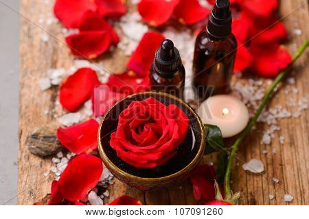 Red rose petals with roses in bowl with pile of salt ,stones on old wooden board